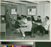 Man leaning against a desk with students in desks