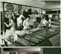 Kitchen with three meal servers preparing food
