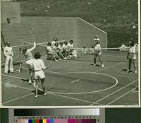 Female students playing badminton on outdoor sports court