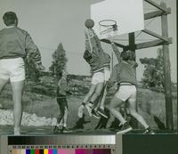 Group of male students playing basketball on an outdoor court