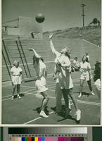 Group of female students playing basketball on an outdoor court