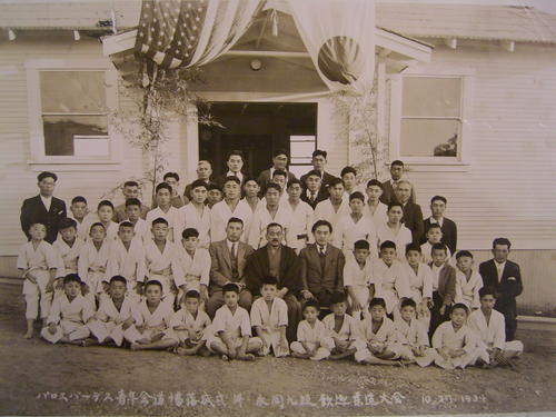 Image shows group portrait of men and boys in front of the single-story wooden structure with American and Japanese flags hanging at the entrance.  The young boys are in white judo uniforms and the men are mostly in suits.  Identified at center, wearing a kimono and dark jacket and a moustache is Hideichi Nagaoka (aka Shuichi Nagaoka).  To the right of Hideichi Nagaoka is Toshitaka Yamauchi, the head judo instructor.  Sadahei Hirose is in the fourth row (from front to back), second from the right.  Ninth belt Hideichi Nagaoka was an invited guest at the first Youth Judo competition, an event held to commemorate the opening of the Youth Judo Club in Palos Verdes., Library has digital image only, courtesy of Mutsuo Hirose., Hideichi Nagaoka contributed to the development of Kodokan judo.