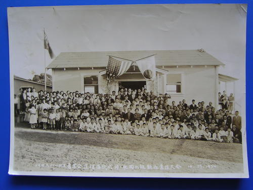 Image shows group portrait of men, women and children in front of the single-story wooden structure with American and Japanese flags hanging at the entrance.  Many of the young boys are wearing white judo uniforms.  Identified at center, wearing a kimono and dark jacket and a moustache is Hideichi Nagaoka (aka Shuichi Nagaoka). To his right is Sadahei Hirose wearing a dark suit.  Wearing a light colored suit directly to the right of Sadahei Hirose is Toshitaka Yamauchi, head judo instructor.  Setsuzo Ota, assistant judo instructor, is seated to the left of Hideichi Nagaoka.  Ninth belt Hideichi Nagaoka was an invited guest at the first Youth Judo competition, an event held to commemorate the opening of the Youth Judo Club in Palos Verdes., Library has digital image only, courtesy of Mutsuo Hirose., Hideichi Nagaoka was a well-known judo instructor of Kodokan, and Toshitaka Yamauchi taught judo in the Gardena area in the 1930s.