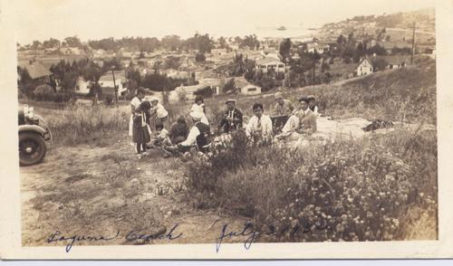 "Image shows Hatashita family at center gathered around a picnic blanket on a dirt-covered slope. Some children and adults are wearing caps. Visible in the foreground are plants, bushes, and at left, a partial view of the front of an automobile. Scattered houses, utility poles, and matured trees are visible in the background.  Handwritten at bottom in blue ink is ""Laguna Beach, July 3, 1932."", Library has digital image only, courtesy of Diane Takenaga."