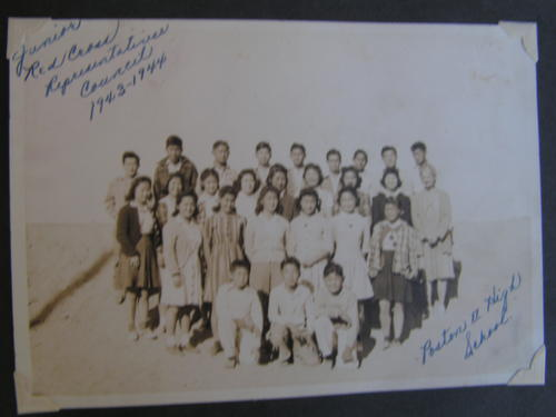 Image shows framed photo depicting group of Japanese American boys and girls in an outdoor setting at Poston II High School.  A Caucasian woman is standing on the third row from the bottom at the far right., Library has digital image only, courtesy of Hideko Shono.