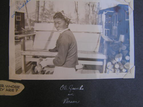 "Image shows framed photo depicting a young woman with her hair under a kerchief pictured from the side, and in front of a bench and bucket.  Houses are visible at right and left and in the distance.  A woodpile is visible to the right.  Hideko Shono received the photo from her friend Junko while Junko was in Jerome, Arkansas. Hideko Shono and Junko lived near each in San Pedro prior to being sent to camp. Photo inscribed in black ink in the top left corner ""To: Hideko"" and ""Love Junko"" at bottom right., Library has digital image only, courtesy of Hideko Shono."