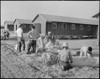 """Poston, Arizona. Evacuees of Japanese ancestry are filling their ticks with..."