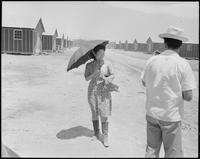 """""""Poston, Arizona. This evacuee is fortified with an umbrella for protection..."""