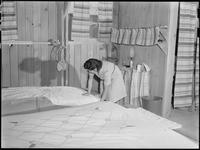 """Poston, Arizona. Mrs. Iwasaki tidies up her home at this War Relocation Authority..."