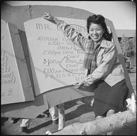 """Poston, Arizona. New Year's Fair. Pretty Nami Nadaoka is shown with the program..."